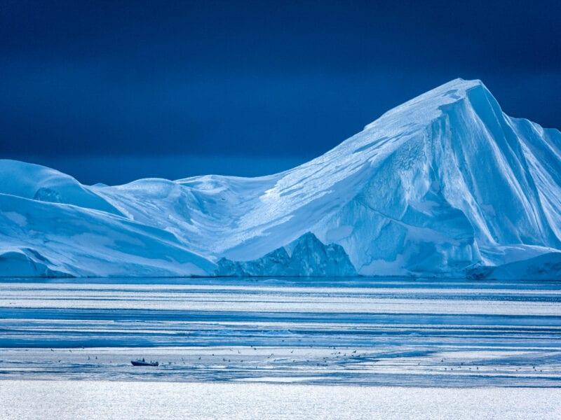 Hinter einem spektakulären Eisberg zieht an einem Tag im Februar ein schwerer Wintersturm auf - Westgrönland