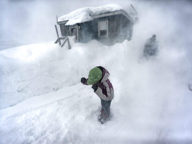 Priska im Schneesturm, doch der Wind kommt nicht aus der Natur, sondern vom Helikopter, der das kleine Dorf im Winter einmal pro Woche versorgt - Ostgrönland
