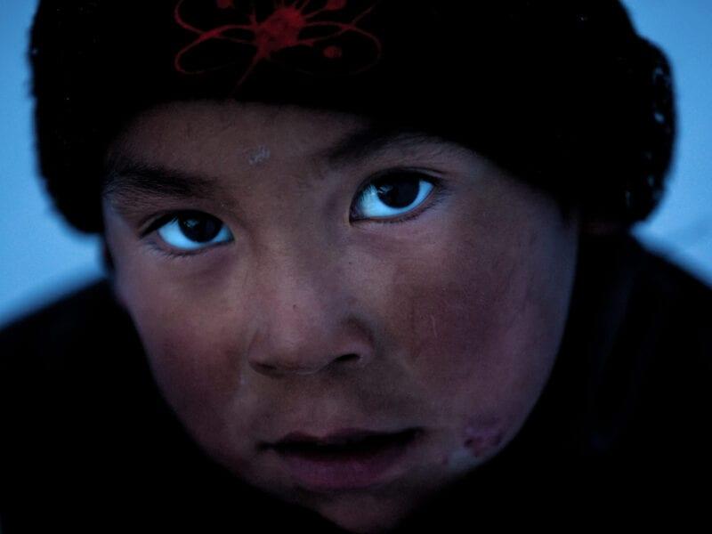 Vitus liegt, erschöpft vom Spiel, im Schnee. In seinen Augen spiegelt sich der dunkle, kalte Winterhimmel - Ostgrönland
