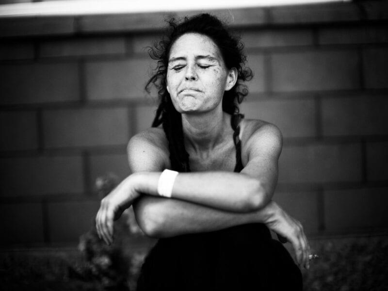 0.000 Amerikaner sterben jährlich durch den Missbrauch von Drogen und Schmerzmitteln. Die junge Frau sitzt allein in brütender Hitze auf dem Parkplatz einer McDonald's-Filiale an der mexikanischen Grenze, Arizona 2017